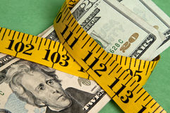 Holiday on a Budget. Money squeezed by a measuring tape representing a tight holiday budget Stock Photos