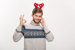 Holiday and Business Concept - Young handsome man talking on phone and giving ok sign. Holiday and Business Concept - Young handsome man talking on phone and Stock Photography