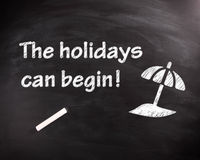The Holiday can Begin Phrase on Black Chalkboard Stock Photo