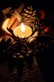 Holiday candle in the dark. A candle is an ignitable wick embedded in wax or another flammable solid substance such as tallow that provides light, and in some Royalty Free Stock Images