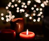 Holiday candle light. Lit candles in front of a holiday tree with lights blurred in background Royalty Free Stock Photography