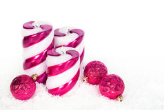 Holiday candles and Christmas ornaments on snow stock image