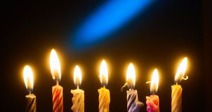 Holiday candles in a row. On dark background Stock Images
