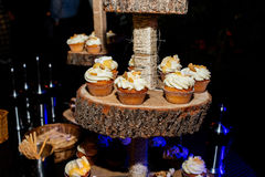 Holiday candy bar. Candy bar served with cupcakes with cream. And biscuits on wooden stump Royalty Free Stock Photo