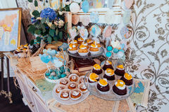Holiday candy bar. Cupcakes with cream and fruits and blue and white cake pops decorated with paper hearts on wedd candy bar Royalty Free Stock Photo