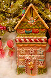 Holiday Candy Lollipop House. A candy house and lollypops sit on sparkling fake snow underneath a Christmas tree at holiday time stock image