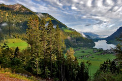 Holiday card. Lake, meadows and a village in Switzerland mountains stock photos