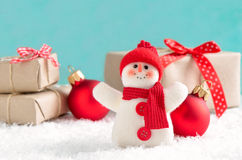 Holiday card. Cute felt snowman standing in a snow with presents and red balls Stock Photo