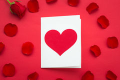 Holiday Card. Heart for Valentines day. Close up Small White Card with I Love You Message and Red Rose Flower on Top of the red ba Royalty Free Stock Photos