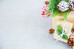Holiday Cristmas Card. Holiday card with present boxes wrapped in kraft paper, Fir Branches and Festive Decoration on White Table. Christmas Greeting Background Stock Images
