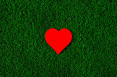Holiday card: red paper heart lies on a green grass Stock Image