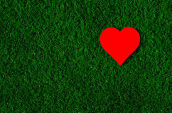 Holiday card: red paper heart lies on a green grass Royalty Free Stock Photo