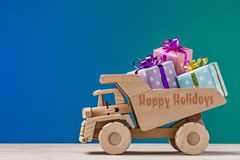 Happy Holidays. Wooden dump truck with gifts. royalty free stock image