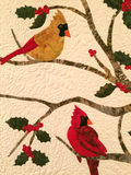 Holiday cardinal and holly cotton fabric quilt. Quilted male and female cardinals on holly tree quilt design exhibited in Arkansas Historic Museum Stock Photo