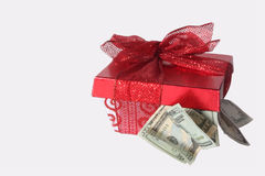 Holiday Cash. White gift box with red lid and lace ribbon with cash falling out. Copy space stock photography