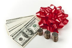 Holiday cash red bow US currency. Holiday cash money hundred dollar bills and stack of coins quarters with red bow on white background Royalty Free Stock Photos