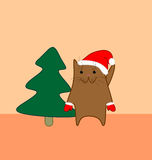 Holiday cat. Cute brown cat with pink nose in Santas red hat an red mittens on light orange background near the spruce Royalty Free Illustration