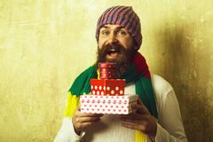 Holiday celebration and shopping. Christmas and birthday. Hipster with present box in hat. Guy with happy face and gift pack. Man with long beard in colorful stock photos
