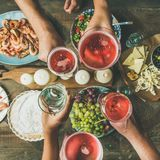 Flat-lay of friends hands eating and drinking together, square crop Royalty Free Stock Photo