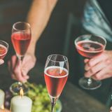 People having party, gathering, celebrating with rose champaign, square crop. Holiday celebration table setting with food. Friends hands eating and drinking Royalty Free Stock Image