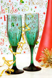 Holiday Cheer. Two green wine glasses and a red wine bottle with a cheerful holiday background stock images