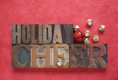 Holiday cheer. The words holiday cheer with bells on a red textured background stock images