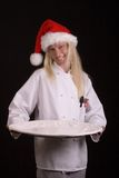 Holiday Chef. Assertive posed uniformed female Chef in a Santa hat holding a large white platter Stock Photography