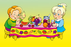 Boy and girl feasting at the table Stock Photo