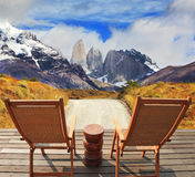 The holiday in Chile. Wooden chairs in the park Torres del Paine. On the horizon is visible snow-covered rocky mountain. Pleasant holiday in Chile Stock Image
