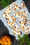 Holiday chocolate bark with dried fruits and nuts on a dark wood background. Top view. Dessert recipe for judaic holiday Tu Bishva Stock Photo