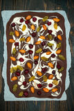 Holiday chocolate bark with dried fruits and nuts on a dark wood background. Top view. Dessert recipe for judaic holiday Tu Bishva Royalty Free Stock Images