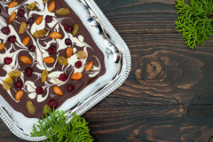 Holiday chocolate bark with dried fruits and nuts on a dark wood background. Top view. Dessert recipe for judaic holiday Tu Bishva Royalty Free Stock Image