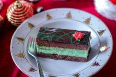 Holiday chocolate mint cake. Slice of holiday chocolate mint cake on a festive white plate with gold Christmas trees Stock Image