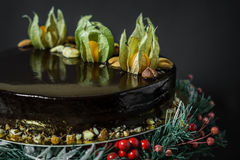 Holiday chocolate mousse cake. With decoration on a stand of fir-tree with berries on a black background Royalty Free Stock Image
