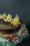 Holiday chocolate mousse cake. With winter decoration on a stand of fir-tree with berries on a black background Stock Photos