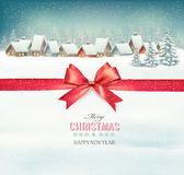Holiday Christmas background with a village and a red bow stock image