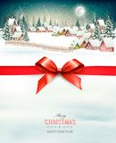 Holiday Christmas background with a winter village and  red bow. Royalty Free Stock Images