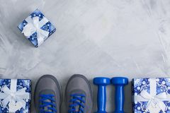 Holiday christmas birthday party sport flat lay composition. With gray shoes, blue dumbbells and blue gifts on gray concrete background. Top view, horizontal royalty free stock image