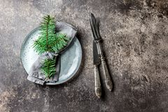Holiday Christmas food background, cutlery, plate, napkin with ring and Christmas tree branch, table setting in silver. Tone, stone background Royalty Free Stock Photo