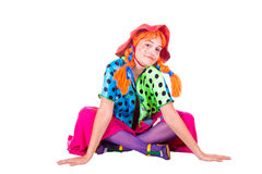 Holiday, clown girl. A girl dressed as a clown red. White background. Studio photography Stock Photography