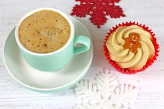 Holiday Coffee and cupcake on a rustic white wood background. Royalty Free Stock Image