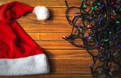 Holiday colorful lights of garland, santa claus hat. Christmas background. Top view stock image
