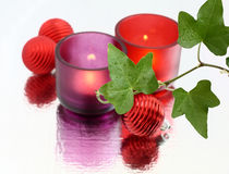 Holiday composition. Balls and candles behind ivy branch Stock Photos