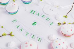 Holiday composition of Happy Easter lettering, branches with young shoots of greenery, decorated cupcakes, merengue sweets, bird f. Igure on wooden background Stock Photos