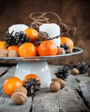 Holiday Composition with Tangerines, Pine cones, Walnuts on Wood Royalty Free Stock Photography