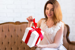 Holiday concept - beautiful woman opening gift box. At home Royalty Free Stock Image