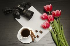 Holiday concept. Bouquet of pink tulips, dslr camera, cup of coffee, cinnamon, star anise and sheet of paper on a black wooden stock photo