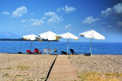 Relax concept, empty beach with parasols and chairs stock images