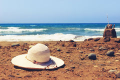Holiday concept with hat and sandcastle on the seaside. Stock Photo