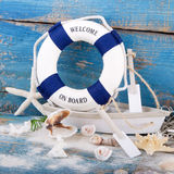 Holiday concept - maritime decoration - Toy boat with a blue life bouy. Toy boat with a blue life bouy - welcome on board. Holiday concept - maritime decoration royalty free stock photos